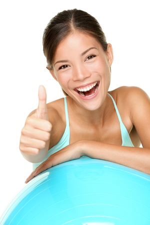 thumbs up woman: Fitness woman pilates. Fitness girl on exercise ball giving thumbs up with fresh energy smiling happy. Fit multicultural mixed race Asian Caucasian female fitness model isolated on white background.