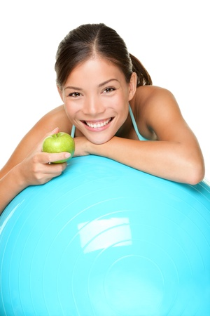 Sport fitness woman on exercise pilates ball eating an apple relaxing taking a break. Smiling happy multiracial female fitness model isolated on white background Stock Photo - 11286013