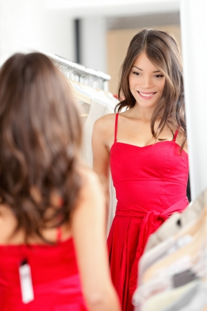Woman trying on dress clothes. Beautiful young woman in clothing store looking at mirror buying new red dress. Gorgeous mixed race Caucasian  Chinese Asian female model in clothes shop smiling happy.