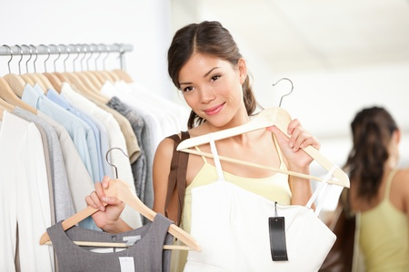 Woman shopping buying new dress in clothing shop choosing between two dresses. Beautiful multiracial caucasian / chinese asian female model looking in mirror smiling happy in clothing store.