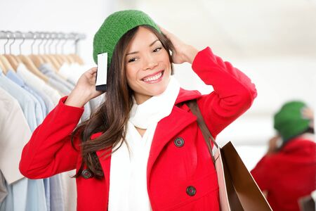 winter fashion: Hat woman. Shopper trying on hat looking in mirror in clothing shop. Beautiful smiling Asian Caucasian female model on shopping trip.