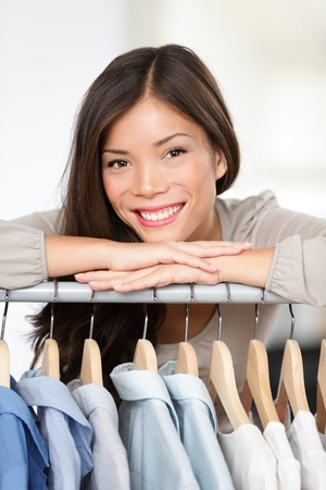 boutique shop: Small clothing shop owner. Portrait closeup of young woman clothes store business owner standing in her shop behind clothing rack smiling happy. Beautiful smiling mixed race Asian Caucasian female model.