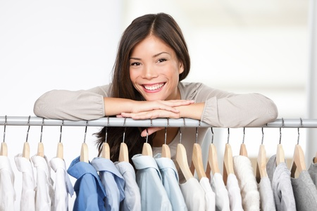 retailer: Business owner - clothes store. Young female business owner in her shop behind clothes rack smiling proud and happy. Multicultural Caucasian  Asian female model.