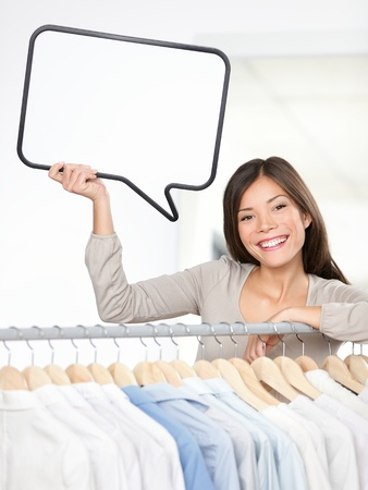salesperson: Shopping sign woman in clothing store. Small clothes business owner with speech bubble sign smiling happy behind clothes rack. Beautiful young Asian Caucasian young woman,