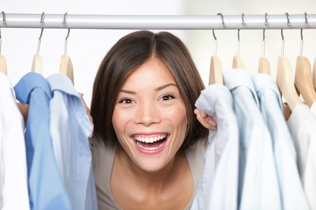 Happy shopping. Woman shopper or shop owner peeking out through clothing in clothes rack. Excited multicultural Asian  Caucasian woman smiling happy in shop.