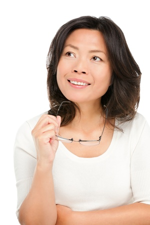 Thinking middle aged mature Asian woman looking up at copy space. Pensive mid age Chinese asian woman in her early 50s isolated on white background.