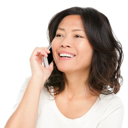 中年のスマート フォンでアジアの女性。美しい成熟した中国アジア女性の白い背景で隔離の携帯電話で話しています。