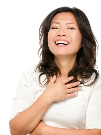 Laughing mature middle aged Asian woman joyful and cheerful. Chinese Asian woman in her early fifties isolated on white background.