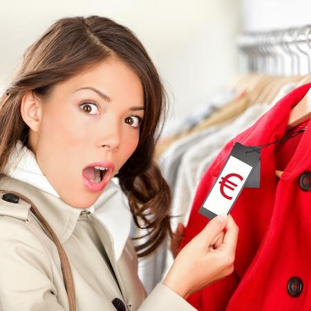 Comprador mujer en shock y sorprendida por los precios de ropa de gran venta en una tienda de ropa.