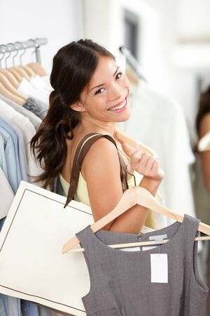 Shopping woman smiling happy holding shopping bag and clothes inside in clothing retail store. Beautiful brunette female model indoors. Banco de Imagens