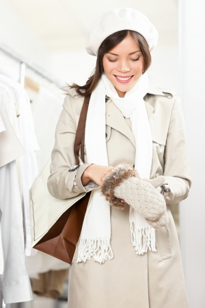 winter clothes: Shopping woman trying winter gloves in clothes store.  Stock Photo