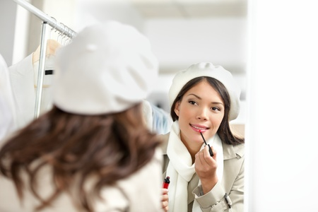 clothing store: Lipstick woman putting lipstick makeup in clothing store while shopping.  Stock Photo