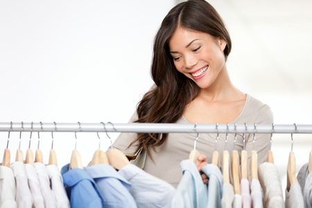 Woman shopping clothes in clothing store looking at shirts on clothing rack. photo