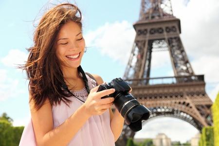 persona viajando: Torre Eiffel de París turística con la cámara tomando fotos frente a la Torre Eiffel, París, Francia. Mujer, joven fotógrafo de unos 20 años. Candid.