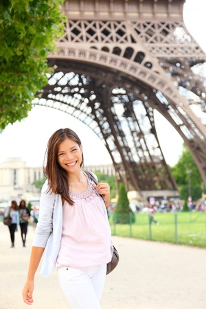 Paris woman by Eiffel Tower. Smiling young happy woman walking in front of the Eiffel Tower, Paris, France. Candid image.