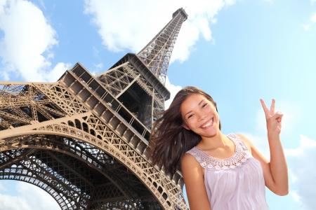 유럽 여행 여행을하는 동안 에펠 탑, 파리, 프랑스 미소 에펠 탑 관광 포즈. 그녀의 20 대 젊은 행복한 흥분 multiracial 아시아 백인 여자.