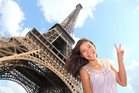 backpackers: Eiffel Tower tourist posing smiling by Eiffel Tower, Paris, France during Europe travel trip. Young happy excited multiracial Asian Caucasian woman in her 20s. Stock Photo