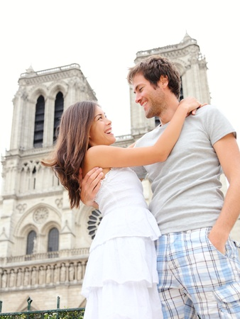 Notre Dame de Paris. Happy young couple in front of Notre Dame Cathedral in Paris, France. Asian woman and Caucasian man.