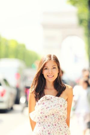 晩春から初夏にバック グラウンドで凱旋門とシャンゼリゼ通り近くを歩いてパリ女性。