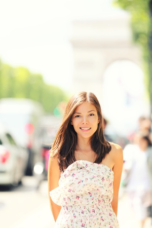 Paris woman walking on Champs-Elysees with Arc de Triomphe in the background in late spring early summer.