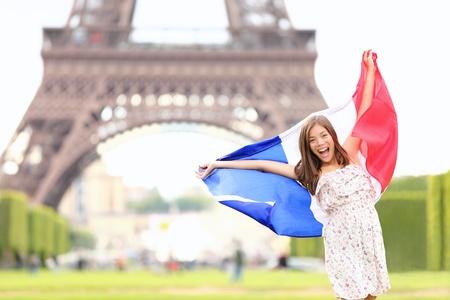 voyage: France - femme drapeau français par la Tour Eiffel, Paris. Concept de voyage en France avec jeune fille excitée et heureuse tenant le drapeau français. Banque d'images