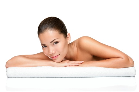 Spa beauty skin treatment woman on white towel. Gorgeous beutiful multiracial Caucasian  Asian female model with perfect skin lying on towel having beauty treatment at spa. Young woman in her 20s isolated on white background. photo