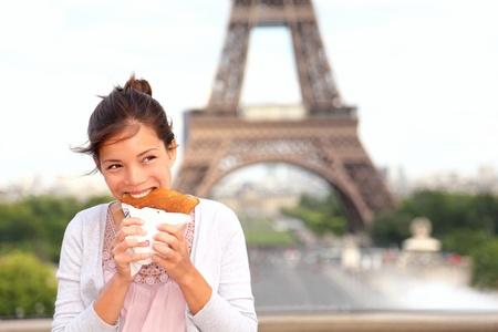 Paris woman eating pancake in front of Eiffel Tower, Paris, France during europe travel