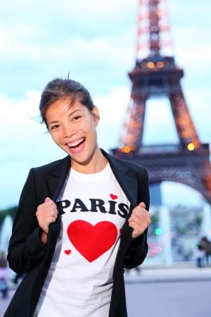 voyage: Paris Tour Eiffel femme heureuse et excitée en face de la Tour Eiffel, Paris, France.