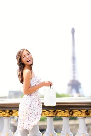 Paris woman happy and smiling - Eiffel Tower in background. Beautiful joyful young multiracial woman enjoying her Paris travel. photo