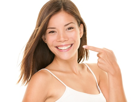 Dental teeth - perfect smile woman pointing at toothy smile looking happy at camera.  photo