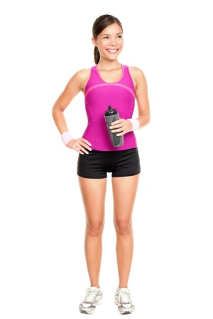 instructor: Asian fitness woman model standing in sporty gym clothing smiling happy holding water bottle.  Stock Photo