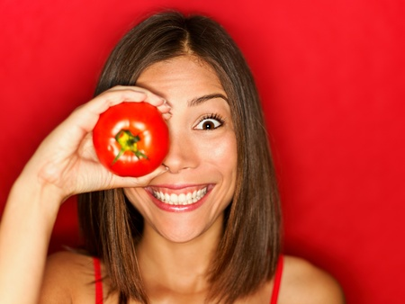 healthy looking: Funny food woman with red tomato smiling happy.  Stock Photo