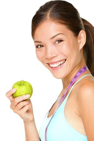 Healthy lifestyle. Fitness woman eating apple wearing measuring tape.  Standard-Bild