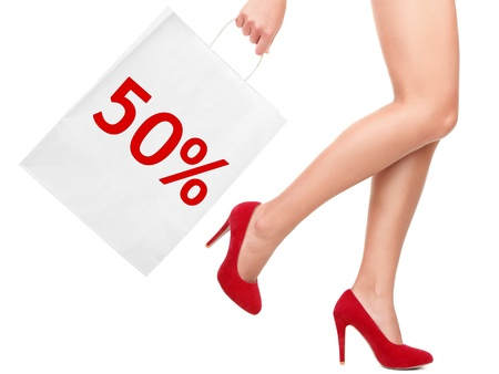 sales person: Sale rebate shopping bag. Shopper showing 50% rebate sign on shopping bag walking with sexy legs and red high heels. Isolated on white background.