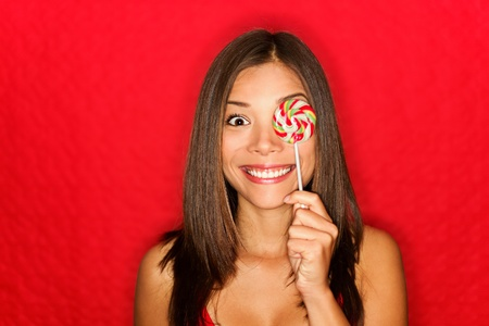 Girl cute funny portrait holding lollipop smiling on red background.  photo