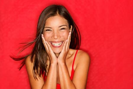 femme qui rit: Bonne fille excit�e. Jeune femme souriante tr�s heureux de t�te tenue surpris d'�tre surpris sur fond rouge.