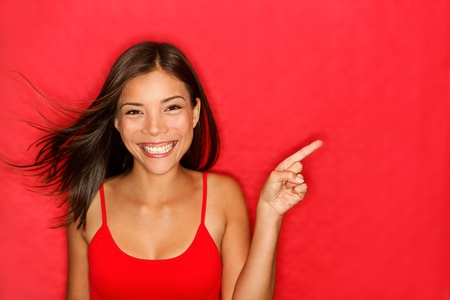 woman showing pointing on red background.  Standard-Bild
