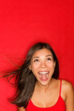 surprised screaming woman looking up at copy space on red background. photo