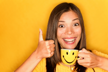 Woman drinking coffee happy giving thumbs up smiling enjoying her morning coffee on yellow background. photo