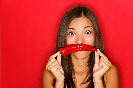 chili woman funny on red background holding red chili pepper vegetables as mustache looking funny at camera. photo