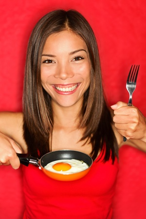 Woman making and eating eggs for breakfast in small pan.  photo
