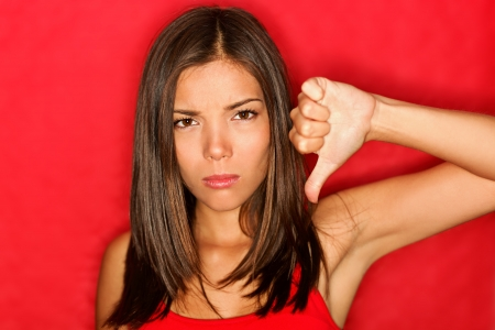 Unhappy woman giving thumbs down gesture looking with negative expression and disapproval. photo
