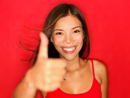 daumen hoch: Daumen hoch wie Frau l�chelt gl�cklich mit nat�rlichen sch�nen L�cheln auf rotem Hintergrund.