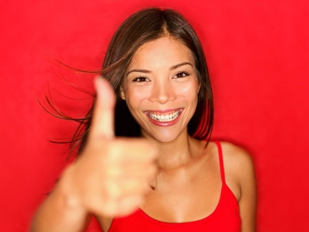 Thumbs up like woman smiling happy with natural beautiful smile on red background. photo