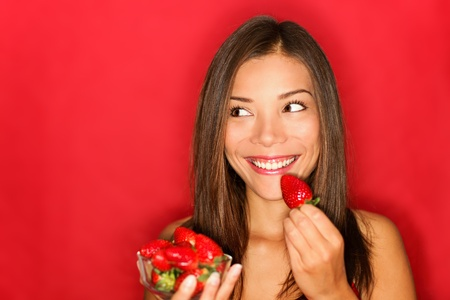 Girl eating strawberries smiling happy looking to the side on red background with copy space.