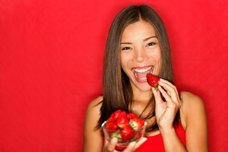 Woman eating strawberries happy. Pretty girl eating healthy snack on red background.  photo