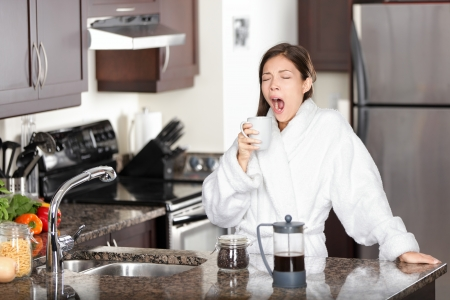 up wake: Yawning coffee woman in morning standing by kitchen table at home.