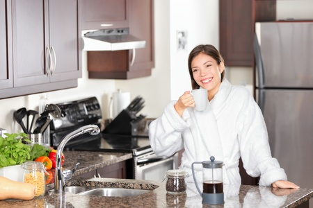 Woman drinking morning coffee in kitchen standing casual in bathrobe.  Stock Photo - 12357178