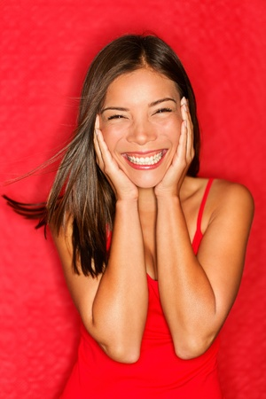 Happy young asian woman excited smiling cheerful holding head in joy.