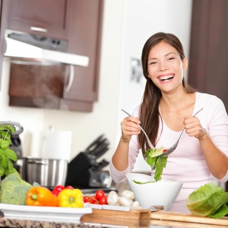 ätande: Kvinna gör sallad i köket ler och skrattar lycklig och glad.